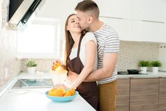 Young Couple in Morning. Portrait of loving young couple cuddling tenderly while cooking breakfast in kitchen on sunny morning Stock Photos