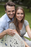 Portrait of loving young couple sitting on chairs in park Royalty Free Stock Photo