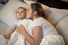 Portrait of loving young mother kissing her baby son before going to sleep. Portrait of loving mother kissing her baby son before going to sleep Royalty Free Stock Photo