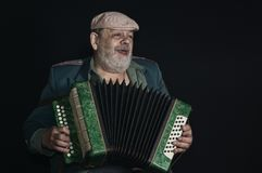 Portrait low key of an old retired military man singing while playing  accordian Royalty Free Stock Photo