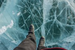 Portrait of man in black long pants and boot shoes on frozen Lake Khovsgol in Mongolia royalty free stock images