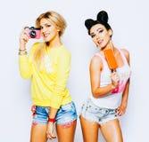 Portrait lumineux d'été de deux amies gaies, de blonde et de brune Ayant l'amusement, appréciant la crème glacée et la prise Image stock