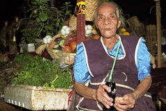 Portrait of lunching senior Latino market vendor. Nicaragua, capital, city Managua: saleswoman of fruit and spices tomatoes, peppers and garlic on the dark Royalty Free Stock Photo