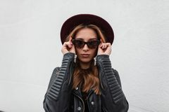 Portrait of luxurious red-haired hipster young woman in dark fashionable sunglasses in purple hat in black stylish leather jacket stock image