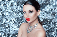 Portrait of luxury glamour young lady on silver background on new year night. Portrait of luxury glamour young lady with red lips on silver background on new stock photo