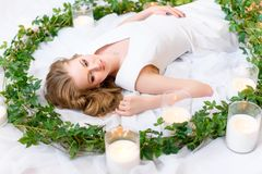 Portrait of a lying girl, thick hair lying messily, gentle glance directed aside, green leaves wreath surrounding her, white stock photography