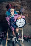 Mad Hatter - Alice in Wonderland. Portrait of Mad Hatter from a fairy tale Alice in Wonderland, with clock. Haloween costume stock photography
