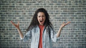 Portrait of mad young woman screaming with anger standing on brick background. Portrait of mad young woman hipster screaming with anger standing on brick stock video