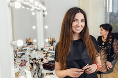 Portrait of makeup artist in beauty salon. Happy young makeup artist holding brush in hands. Visagiste ready to work on a client. Portrait of make-up artist in Stock Photo