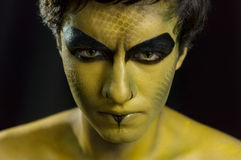 Portrait and makeup with the concept of snake.Photography studio. Angry animal black bodypaint cosmetic details eyes face flakes green halloween human make Stock Images