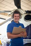 Portrait Of Male Aero Engineer With Clipboard Carrying Out Check. Male Aero Engineer With Clipboard Carrying Out Check On Helicopter In Hangar Royalty Free Stock Photo