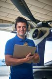 Portrait Of Male Aero Engineer With Clipboard Carrying Out Check. Male Aero Engineer With Clipboard Carrying Out Check On Helicopter In Hangar Stock Photos