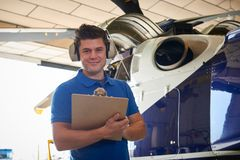 Portrait Of Male Aero Engineer With Clipboard Carrying Out Check. Male Aero Engineer With Clipboard Carrying Out Check On Helicopter In Hangar Royalty Free Stock Photos