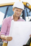 Portrait of male architect holding blueprint at construction site Royalty Free Stock Photography