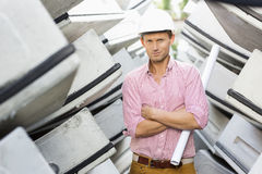 Portrait of male architect holding rolled up blueprint at construction site Stock Images