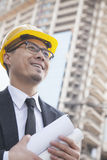 Portrait of male architect on site carrying blueprints Royalty Free Stock Photo
