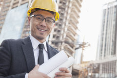 Portrait of male architect on site carrying blueprints Royalty Free Stock Photography