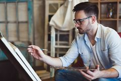 Portrait Of Male Artist Working On Painting In Studio royalty free stock photo