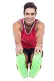 Portrait of male athlete doing stretching exercise. On white background Stock Photos
