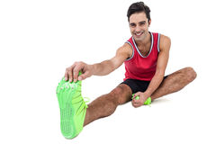 Portrait of male athlete doing stretching exercise. On white background Stock Photography