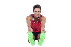 Portrait of male athlete doing stretching exercise. On white background Stock Images