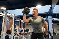 Portrait male athlete trains biceps in gym. View of a fit muscular man holding dumbbell and trainig biceps in modern gym royalty free stock photo