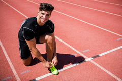 Portrait of male athlete tying her shoe laces on running track Royalty Free Stock Image
