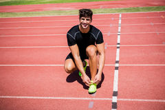 Portrait of male athlete tying her shoe laces on running track Royalty Free Stock Photography