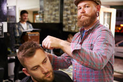 Portrait Of Male Barber Giving Client Haircut In Shop Stock Photo