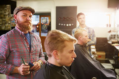 Portrait Of Male Barber Giving Client Haircut In Shop Stock Images