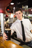 Portrait of male bartender serving beer Royalty Free Stock Photo