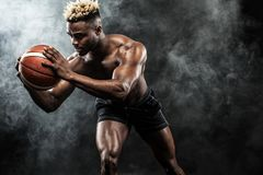 Portrait of afro-american sportsman, basketball player with a ball over black background. Fit young man in sportswear Stock Photos