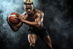 Portrait of afro-american sportsman, basketball player with a ball over black background. Fit young man in sportswear. Portrait of male basketball player with a Stock Photography