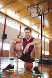 Portrait of male basketball player sitting on ball Royalty Free Stock Photo