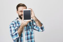 Portrait of male bearded shop assistant covering half-face with tablet to advertise it while smiling broadly and looking. At camera, over gray background. Look Royalty Free Stock Photos