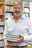 Portrait Of Male Bookshop Owner. Holding Books Stock Photos