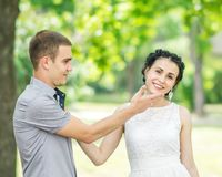 Portrait of male bridegroom touching face of beautiful young female bride in summer park. Couple in love. Emotions and gestures.  Stock Images