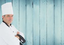 Portrait of male chef cook standing with arms crossed. Against wooden background stock photos