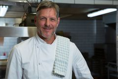 Male chef standing in commercial kitchen. Portrait of male chef standing in commercial kitchen royalty free stock images