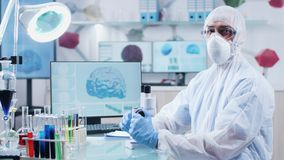 Portrait of male chemist wearing protective clothes, mask and glasses. He is in high end research facility with 3D brain and DNA scans running on displays in stock footage