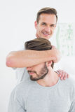 Portrait of a male chiropractor doing neck adjustment Stock Photo