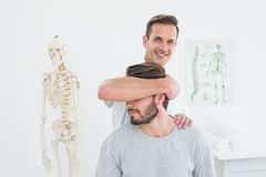 Portrait of a male chiropractor doing neck adjustment Royalty Free Stock Photos