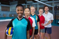 Male coach and volleyball players standing in a row. Portrait of male coach and volleyball players standing in a row royalty free stock images