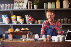 Portrait Of Male Coffee Shop Owner Standing Behind Counter Stock Photography