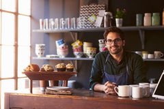 Portrait Of Male Coffee Shop Owner Standing Behind Counter Stock Images