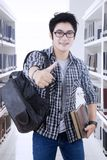 Male college student showing thumb up. Portrait of male college student carrying books while showing thumb up in the library Royalty Free Stock Photos