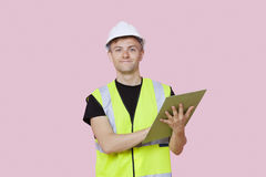 Portrait of a male construction worker with clipboard over pink background Stock Image