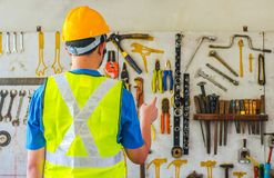 Portrait of a male construction worker in the helmet choosing the many different rusty old tools hanging on a wall. A Portrait of a male construction worker in stock images