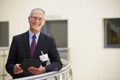 Portrait Of Male Consultant Using Digital Tablet In Hospital Stock Image