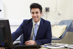 Portrait Of Male Consultant Working At Desk Stock Photography